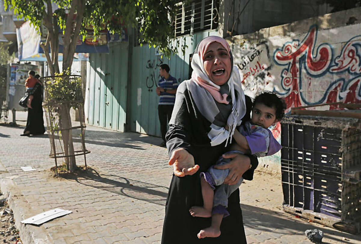 A woman cries as Palestinians flee their homes in the Shajaiyeh neighborhood of Gaza City, after Israel had airdropped leaflets warning people to leave the area, Wednesday, July 16, 2014. A Hamas website says Israel has fired missiles at the homes of four of its senior leaders as it resumed bombardment of Gaza, following a failed Egyptian cease-fire effort. Health officials say the Palestinian death toll in nine days of fighting has reached 204. (AP Photo/Lefteris Pitarakis)