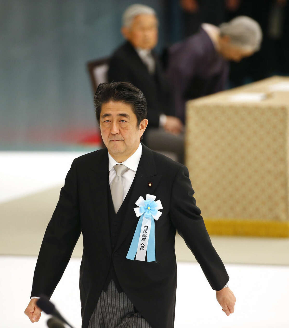 Japanese Prime Minister Shinzo Abe leaves after delivering his remarks during a memorial service at Nippon Budokan martial arts hall in Tokyo, Saturday, Aug. 15, 2015. Japan marked Saturday the 70th anniversary of the end of World War II. Sitting in the background are Emperor Akihito and Empress Michiko. (AP Photo/Shizuo Kambayashi)