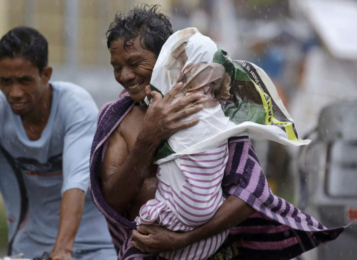 Residents of the slum community of Baseco evacuate to safer grounds at the onslaught of typhoon Rammasun in Manila Wednesday, July 16, 2014 in Manila, Philippines. Typhoon Rammasun left at least seven people dead and knocked out power in many areas Wednesday but the Philippine capital and densely populated northern provinces were spared a direct battering when its fierce winds shifted slightly.(AP Photo/Bullit Marquez)