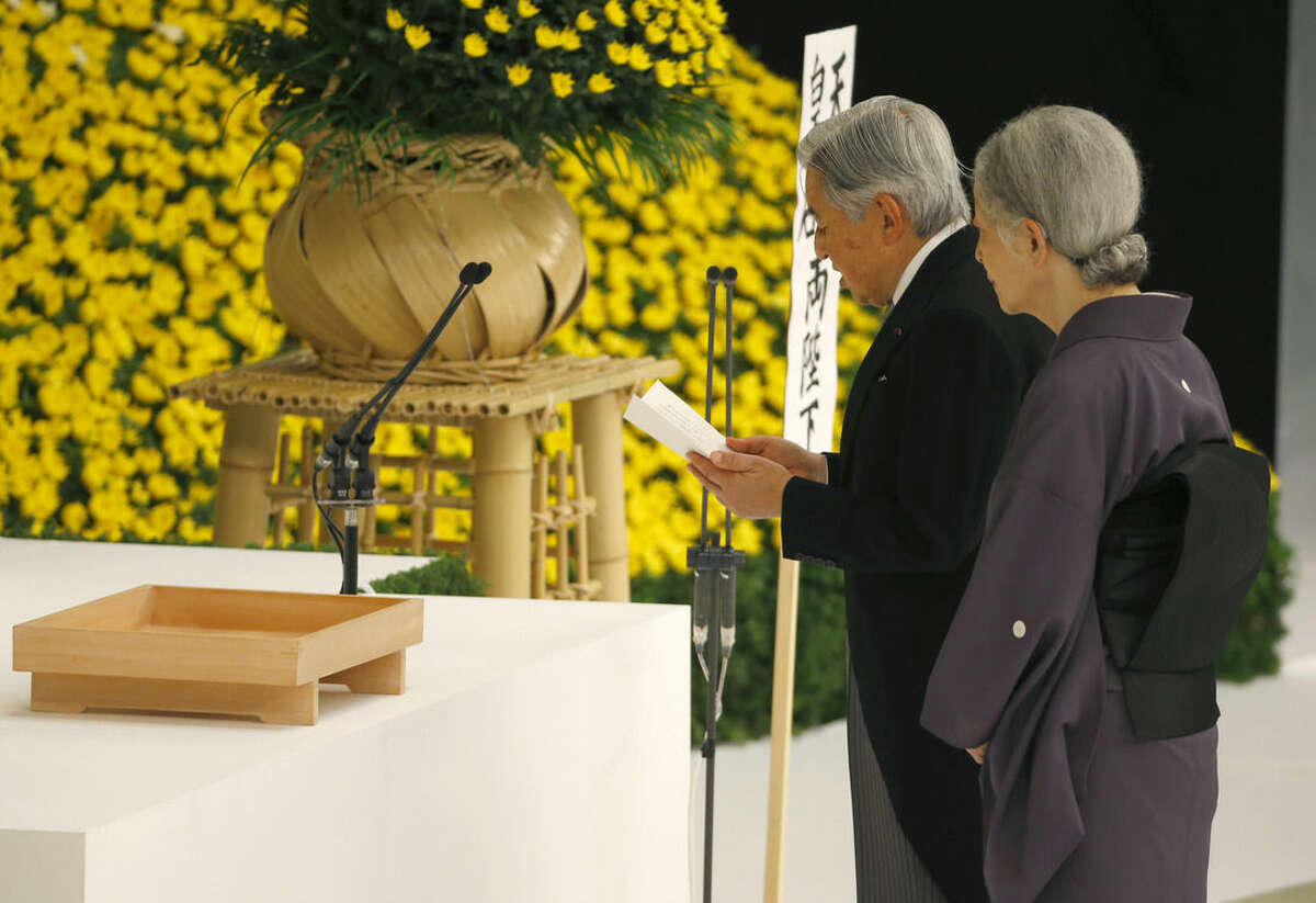 Japan's Emperor Akihito, right, delivers his remarks with Empress Michiko during a memorial service at Nippon Budokan martial arts hall in Tokyo, Saturday, Aug. 15, 2015. Japan marked Saturday the 70th anniversary of the end of World War II. (AP Photo/Shizuo Kambayashi)