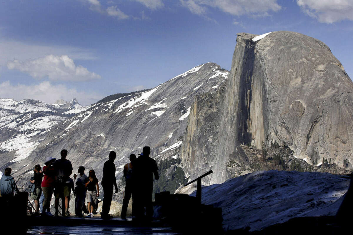 FILE - In this 2005 file photo, visitors view Half Dome from Glacier Point at Yosemite National Park, Calif. Officials say an oak tree limb fell on a tent in the heart of Yosemite National Park killing two young campers early Friday morning, Aug. 14, 2015. Park spokesman Scott Gediman declined to release the ages or any details about the two, describing them only as under age 18. Gediman said the campground is one of the most popular with a view of Half Dome.(AP Photo/Dino Vournas, File)
