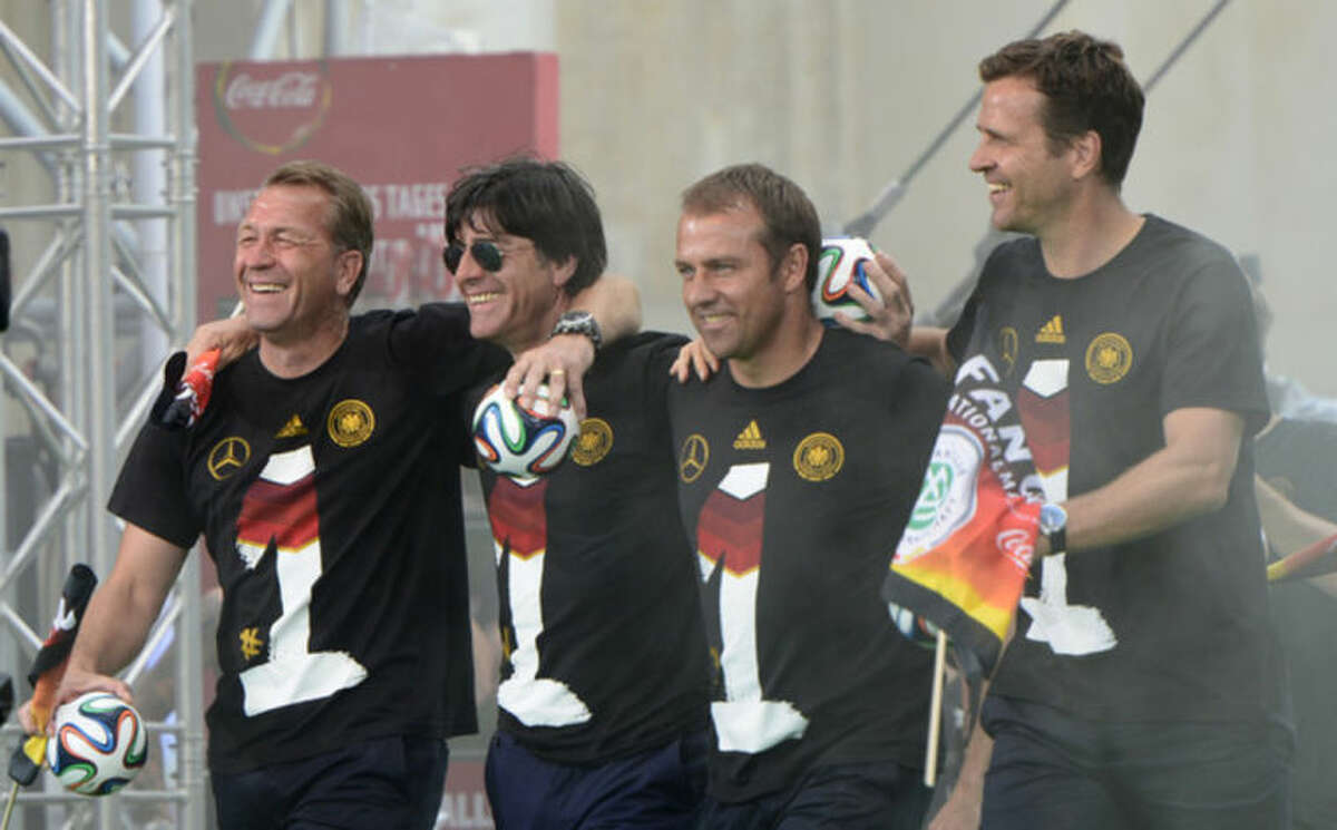 The German coaching team, from left, goalkeeper coach Andreas Koepke, head coach Joachim Loew, assistant coach Hansi Flick and team manager Oliver Bierhoff walk onto the stage after the arrival of the German national soccer team in Berlin Tuesday, July 15, 2014. Germany beat Argentina 1-0 on Sunday to win its fourth World Cup title. (AP Photo/Jens Meyer)