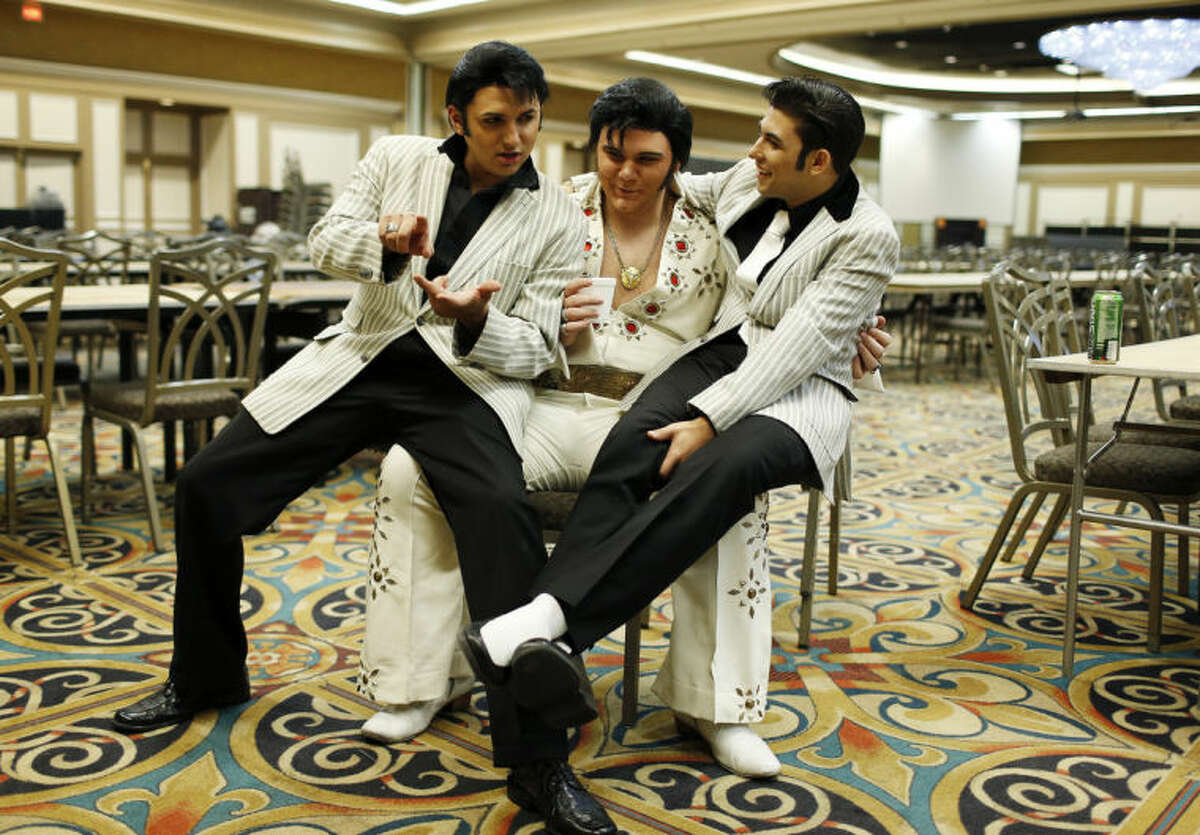 In this July 12, 2014 photo, from left, Daniel Jenkins, Tyler James and Jacob Roman joke around during the Las Vegas Elvis Festival in Las Vegas. The three, along with other Elvis tribute artists, performed in a competition at the convention. (AP Photo/John Locher)
