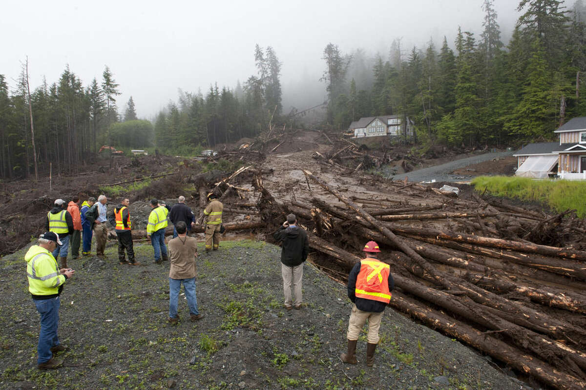 Construction workers and emergency crew members look at the damage caused by a landslide on Kramer Drive, Tuesday, Aug. 18, 2015 in Sitka, Alaska. Homes in the town have been flooded, and there were reports of residents not being able to reach their homes or leave their neighborhood, said a spokesman for the state Department of Homeland Security and Emergency Management. (James Poulson/The Daily Sitka Sentinel via AP) MANDATORY CREDIT
