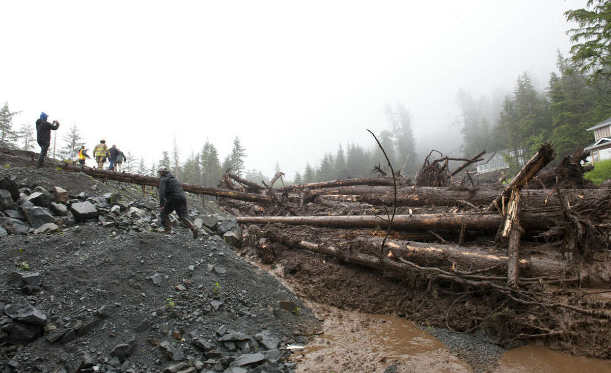 Emergency workers walk around a mud and debris-filled Kramer Drive to the site of a destroyed home Tuesday, Aug. 18, 2015, in Sitka, Alaska. Homes in the town have been flooded, and there were reports of residents not being able to reach their homes or leave their neighborhood, said a spokesman for the state Department of Homeland Security and Emergency Management. (James Poulson/The Daily Sitka Sentinel via AP) MANDATORY CREDIT