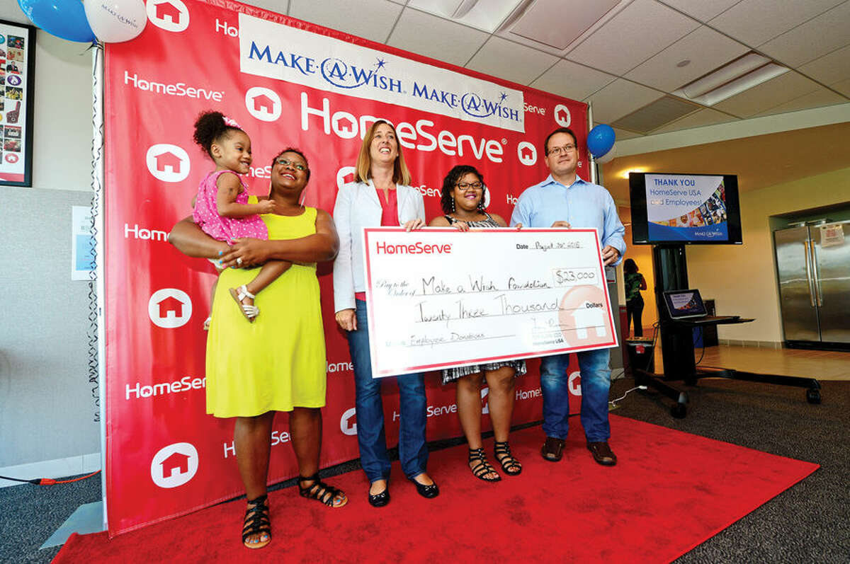 Hour photo / Erik Trautmann Norwalk-based company HomeServe USA CEO Tom Rusin, right, presents a $23,000 donation to the Make-A-Wish foundation and their Development Officer, Maria Arnold, center, while Make-A-Wish recipient Ayasha Cantey, second from right, and her mother, Lashawnda Cantey and sister, Trinidad, 3, participate in the check passing ceremony Thursday morning at HomeServe USA headquarters. The gift to the foundation was a result of HomeServe employees raising nearly $11,500 through several charitable initiatives, which was matched by the company.