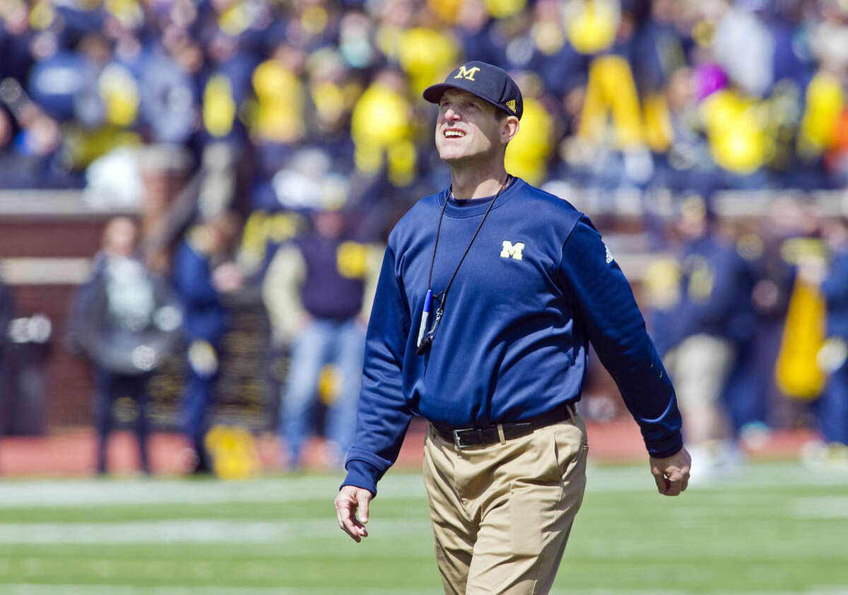 FILE - In this April 4, 2015, file photo, Michigan head coach Jim Harbaugh walks the field between downs during the NCAA college football team's spring game in Ann Arbor, Mich. Now Harbaugh will finally begin coaching the Wolverines in some actual games _ but no matter how this first season in Ann Arbor goes, the quirky, khaki-wearing coach has unified a fractured Michigan fan base. (AP Photo/Tony Ding, File)