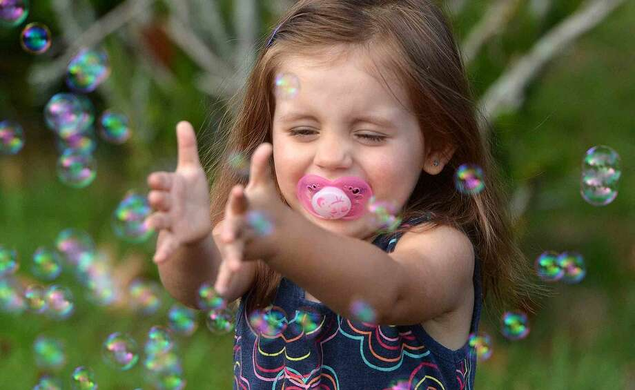 Hour Photo/Alex von Kleydorff 2yr old Maria Koutsimanis trys to catch some bubbles during the 2015 Norwalk Greek Festival at St George Greek Orthodox Church