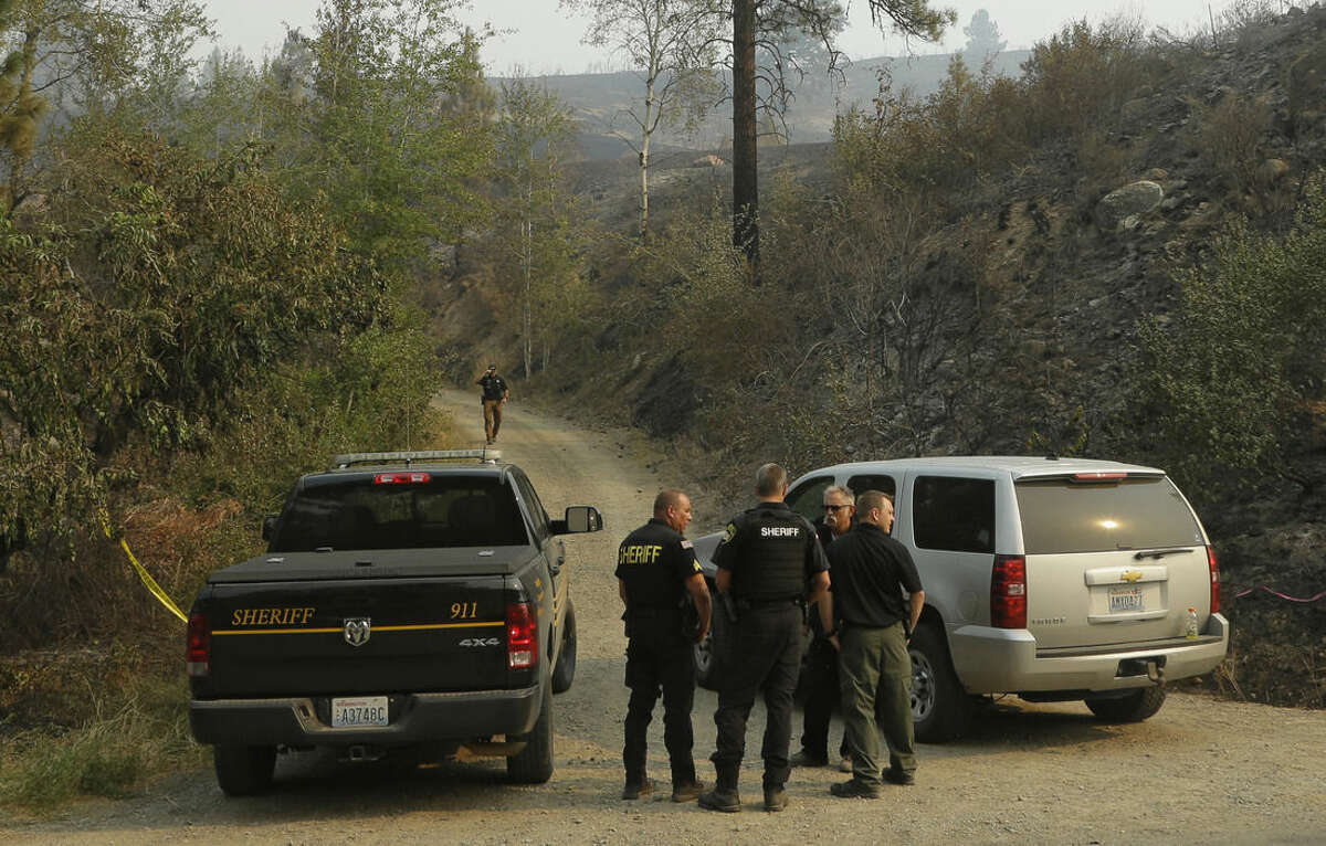 Okanogan County Sheriff's deputies guard the entrance to Woods Canyon Road near Twisp, Wash. Thursday, Aug. 20, 2015. Three firefighters were killed Wednesday along the road while fighting a wildfire. (AP Photo/Ted S. Warren)