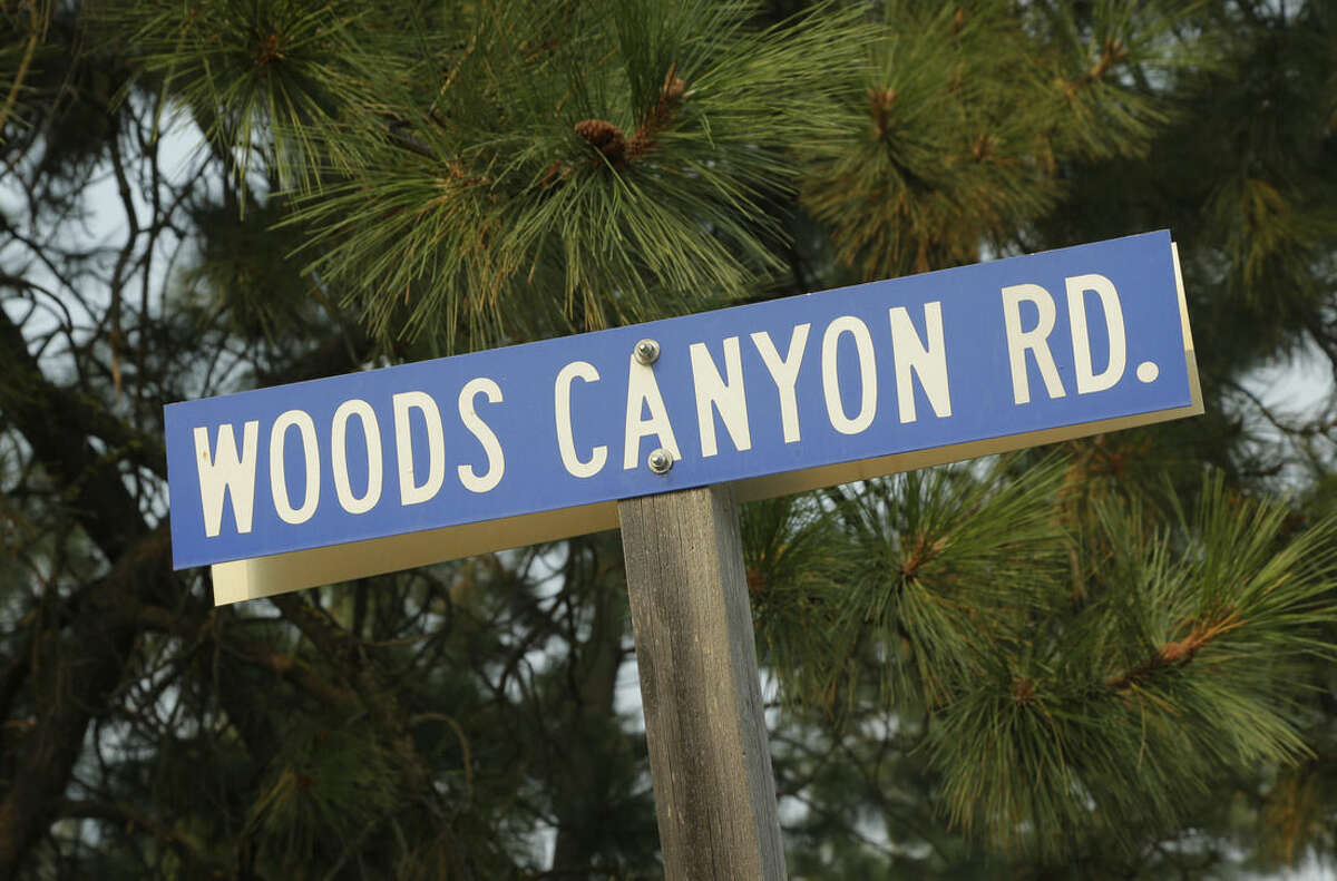 This photo shows a road sign for Woods Canyon Road near Twisp, Wash., Thursday, Aug. 20, 2015. Three firefighters were killed Wednesday along the road while fighting a wildfire. (AP Photo/Ted S. Warren)