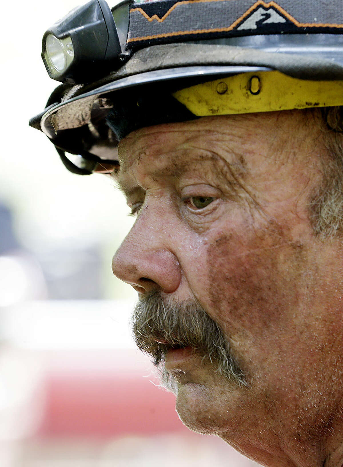 Firefighter Mark Groves, who said he was 32 hours into fighting fire, takes a breather Thursday, Aug. 20, 2015, in Twisp, Wash., a day after three firefighters were killed fighting a wildfire near the town. Authorities say three firefighters died after their vehicle crashed and was apparently caught by a