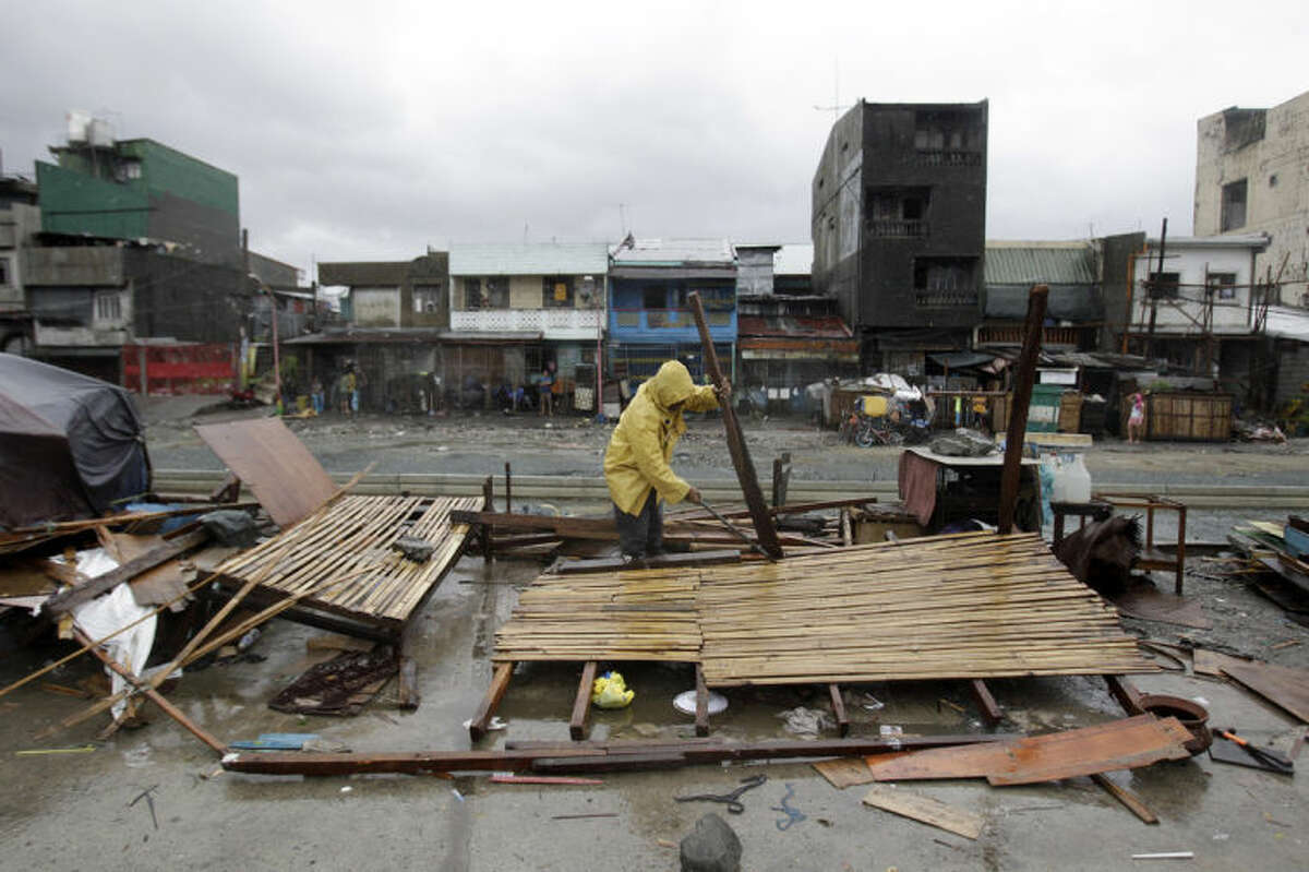 A man salvages what is left of his makeshift house as Typhoon Rammasun batters suburban Navotas, north of Manila, Philippines on Wednesday, July 16, 2014. Typhoon Rammasun knocked out power in many areas but it spared the Philippine capital, Manila, and densely-populated northern provinces from being directly battered Wednesday when its fierce wind shifted slightly away, officials said. (AP Photo/Aaron Favila)