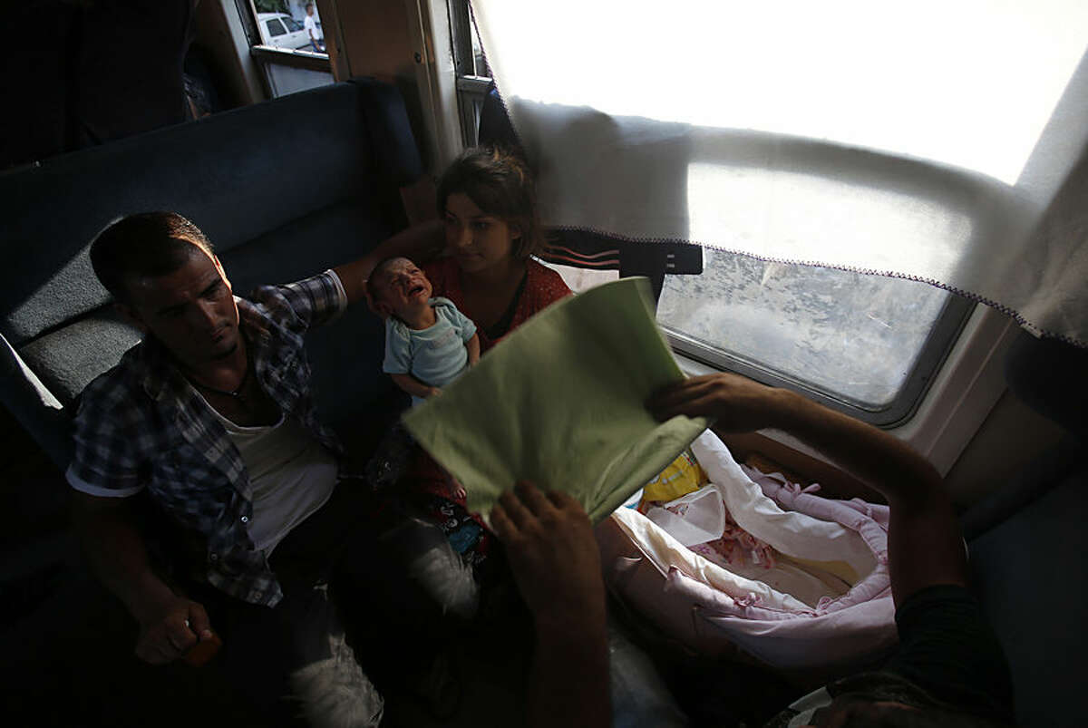 In this Wednesday, Aug. 19, 2015, photo, Amina Asmani, center with her baby travel on train taking them towards Serbia, near the southern Macedonian town of Demir Kapija. Macedonia has become is a major transit route for the migrants heading from Greece to more prosperous European Union countries. Thousands of migrants have been registered passing through the impoverished Balkan country over the past month, double than the month before. (AP Photo/Darko Vojinovic)