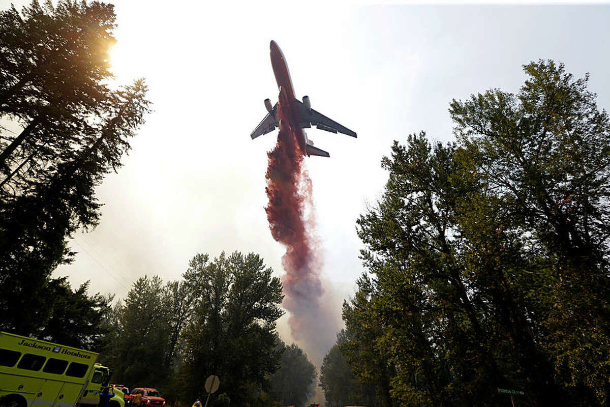 A tanker drops fire retardant on a fire that flared-up Thursday, Aug. 20, 2015, in Twisp, Wash. ildfires rampaged across the drought-choked West on Thursday as authorities scrambled for resources to beat back the flames. (AP Photo/Elaine Thompson)