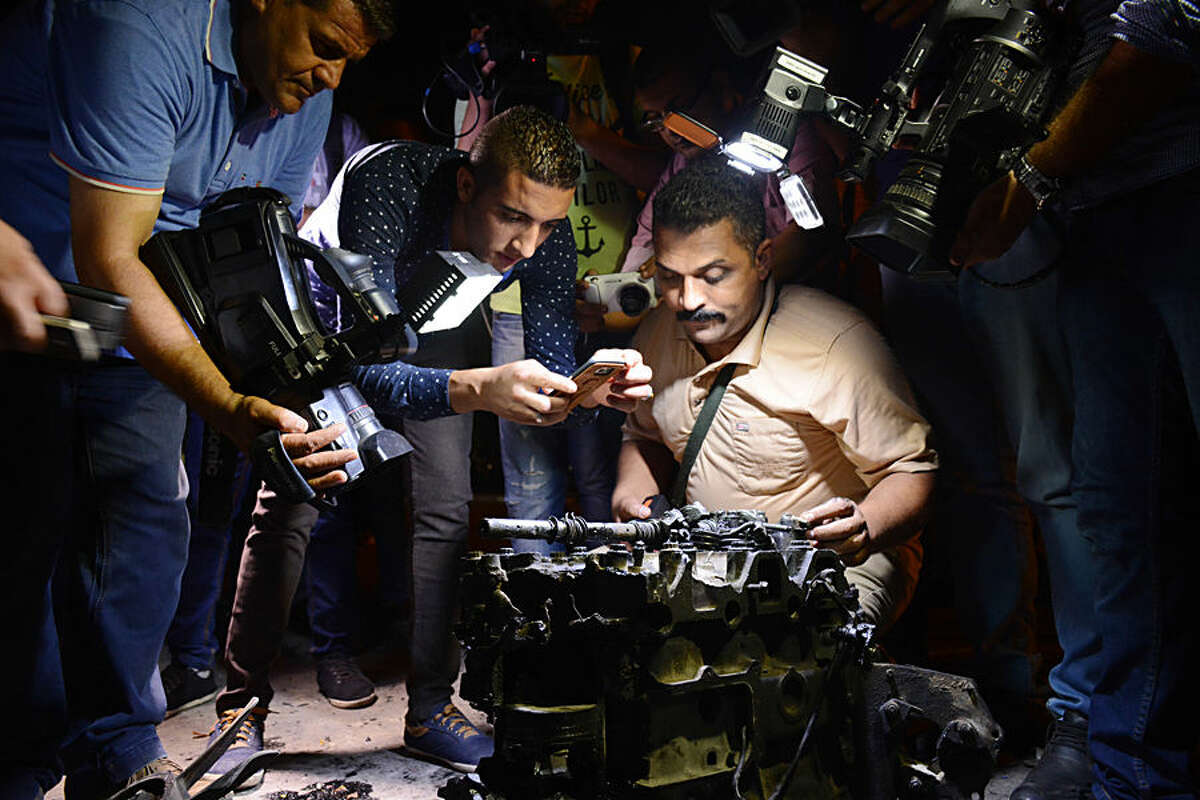 Journalists film and photograph a part from a massive car bomb that exploded early Thursday, Aug. 20, 2015 near a national security building in a popular residential neighborhood in Cairo, wounding several police officers and blowing the facades off nearby buildings, Egyptian security officials said. (AP Photo/ Hisham Abd El Hamed)