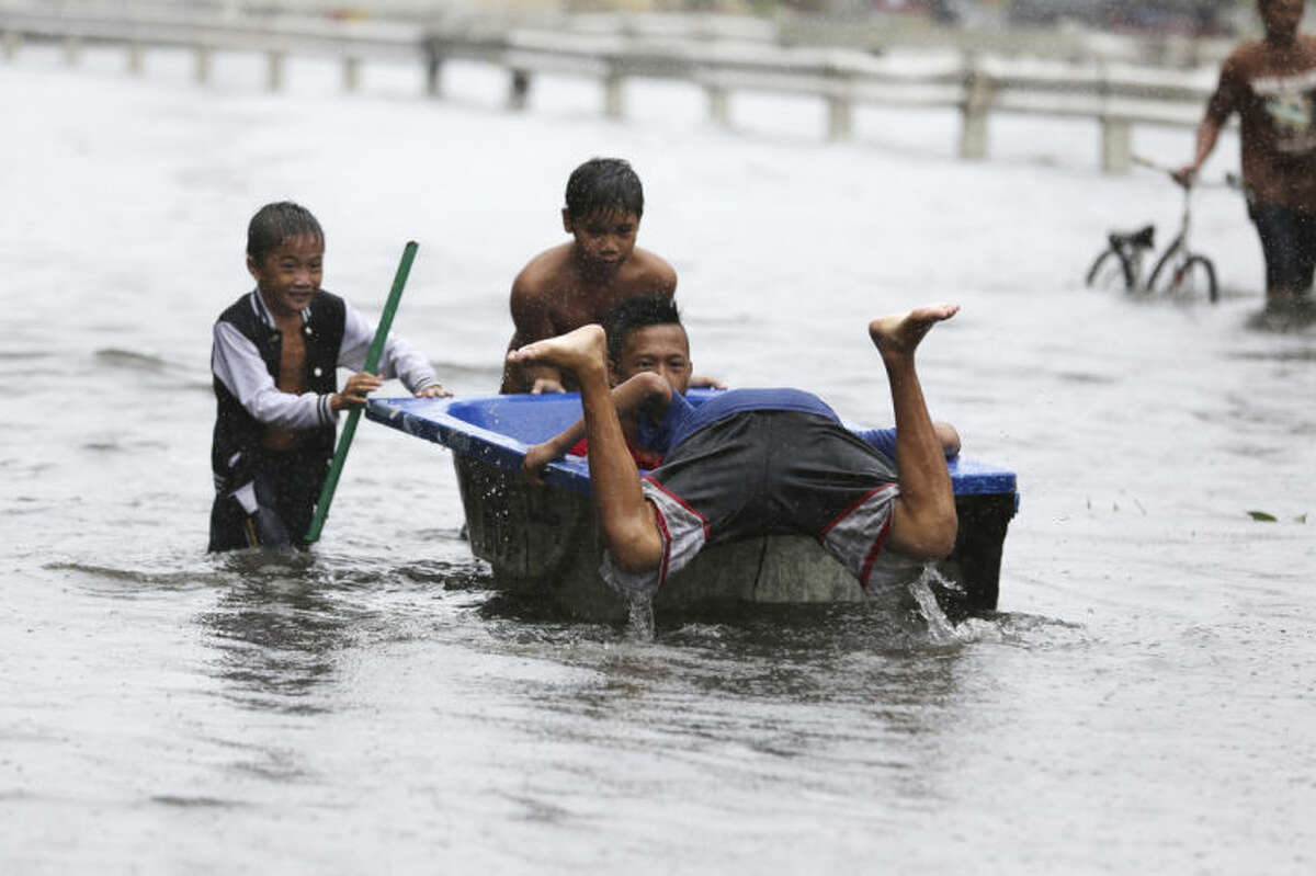 Filipino children play with a bathtub along flooded roads as Typhoon Rammasun batters suburban Navotas, north of Manila, Philippines on Wednesday, July 16, 2014. Typhoon Rammasun knocked out power in many areas but it spared the Philippine capital, Manila, and densely-populated northern provinces from being directly battered Wednesday when its fierce wind shifted slightly away, officials said. (AP Photo/Aaron Favila)