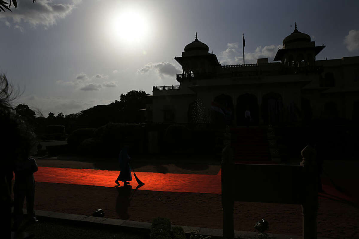 An Indian woman worker sweeps the red carpet laid for head of the states and leaders from Pacific Island countries at Rambagh Palace in Jaipur, India, Friday, Aug. 21, 2015. The Pacific Island leaders are in Jaipur to participate in the Forum for India-Pacific Island Countries (FIPIC) Summit. (AP Photo/Manish Swarup)