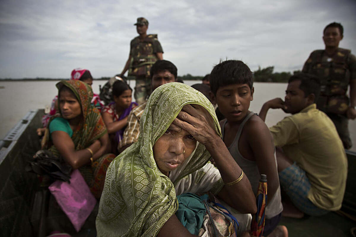 An Indian woman watches from an army boat as she along with others is transported to safer areas from flood affected Jaraguri village, about 160 kilometres (99 miles) west of Gauhati, India, Friday, Aug. 21, 2015. Incessant rainfall in catchment areas have led to rise in water level of the Brahmaputra river and its tributaries, inundating several districts of both Upper and Lower Assam, according to local news reports. (AP Photo/Anupam Nath)