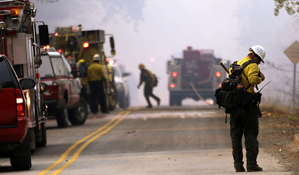 A firefighter runs as another checks gear near the scene of a flare-up Thursday, Aug. 20, 2015, in Twisp, Wash. Authorities say three firefighters died after their vehicle crashed and was apparently caught by a