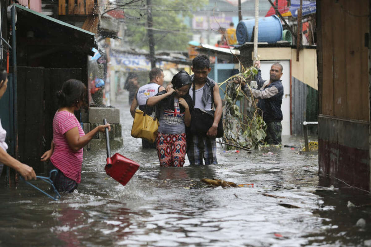 Residents wade through floods as they go back to their home while Typhoon Rammasun batters suburban Quezon city, north of Manila, Philippines on Wednesday, July 16, 2014. Typhoon Rammasun knocked out power in many areas but it spared the Philippine capital, Manila, and densely-populated northern provinces from being directly battered Wednesday when its fierce wind shifted slightly away, officials said. (AP Photo/Aaron Favila)