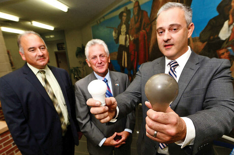 Hour photo / Erik Trautmann Eversource Energy Representative, Ronald Araujo, Mayor Harry Rilling and Councilman John Kydes of the Mayor's Energy and Environment Task Force display a LED and incadescent light bulb to promote the free Light Bulb Swap for residents Saturday, September 19, 2015 in the Community Room of Norwalk City Hallmade possible by a $15,000 Eversource Bright Idea Grant.
