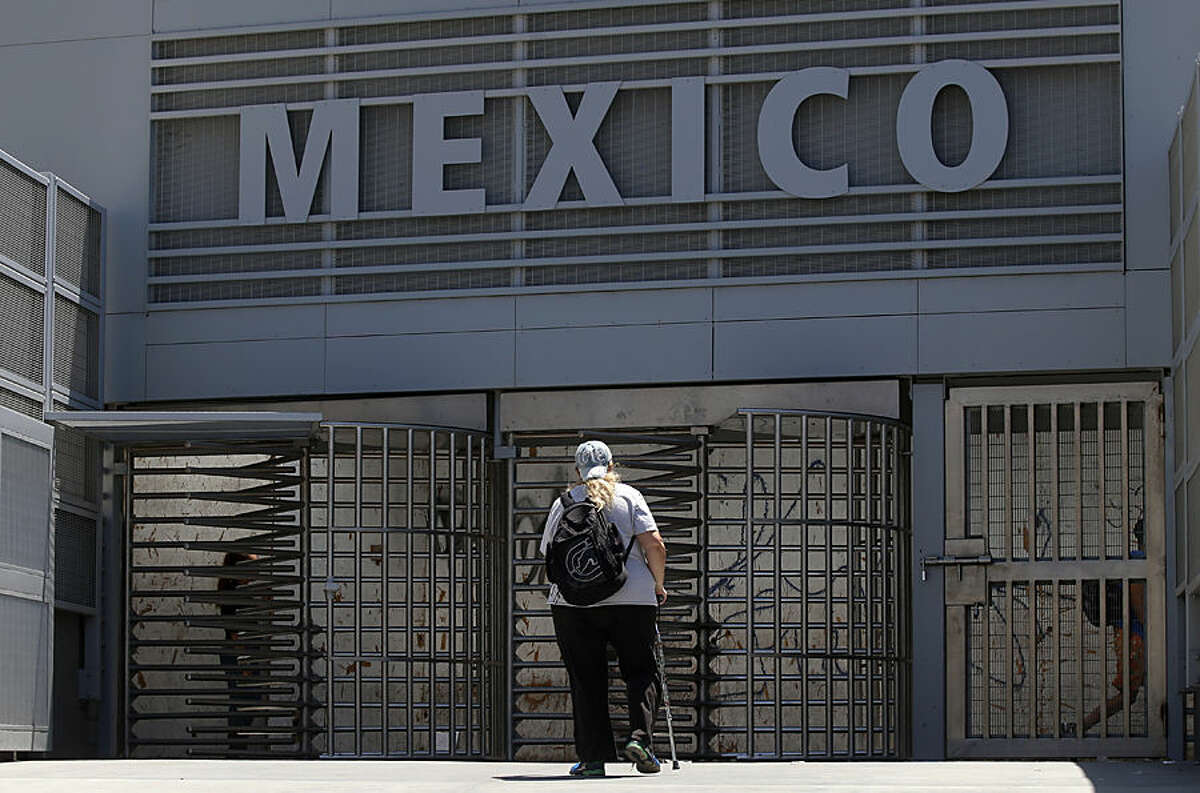 In this Aug. 18, 2015, photo, a woman approaches the entrance to the Mexico border crossing in San Ysidro, Calif. Starting late Wednesday, Aug. 19, pedestrians going to Tijuana from San Diego at the San Ysidro crossing must choose between a line for Mexicans who get waved through, and a line for foreigners. Foreigners must show a passport, fill out a form and, if staying more than a week, pay for a six-month permit. (AP Photo/Lenny Ignelzi)