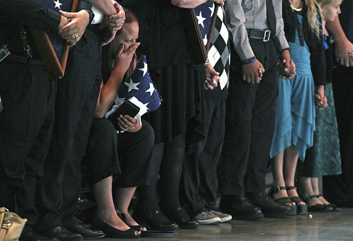 Rachel Howell wife of Carson City Sheriff's Deputy Carl Howell, is overcome with grief and forced to sit as she holds an American flag that draped her husbands casket during his funeral Thursday Aug. 20, 2015 in Reno, Nev. More than 1,000 people stood up in the middle of a funeral Thursday to cheer, applaud and whistle for a slain Carson City sheriff's deputy remembered as both a gentle, funny man and heroic warrior who sacrificed his life to save others. (AP Photo/Lance Iversen)