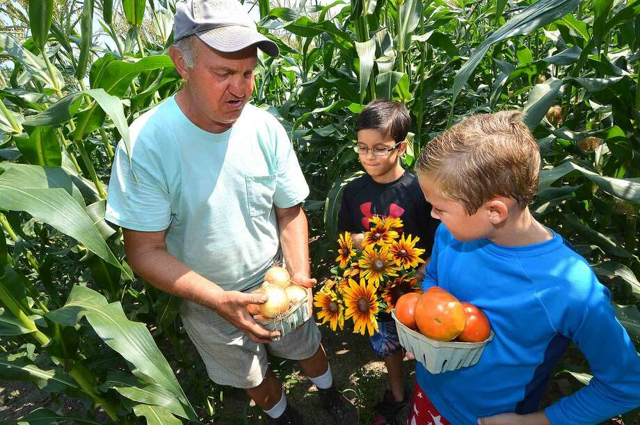 At Offingers Farm, Don Offinger shows 9-year-old Elijah Llanos and 9-year-old Liam Keliehor some vegetables and flowers from his farm.