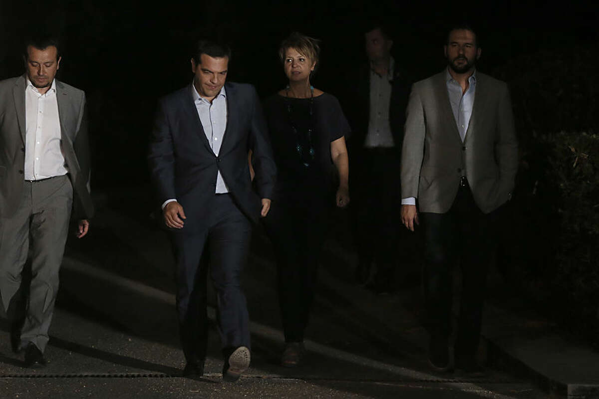 Greek Prime Minister Alexis Tsipras, second left, leaves the Presidential palace after a meeting with Greek President Prokopis Pavlopoulos, in Athens, Thursday, Aug. 20, 2015. Tsipras announced his government's resignation and called early elections Thursday, seeking to consolidate his mandate to implement a new three-year international bailout that sparked a rebellion within his radical left Syriza party. (AP Photo/Petros Giannakouris)