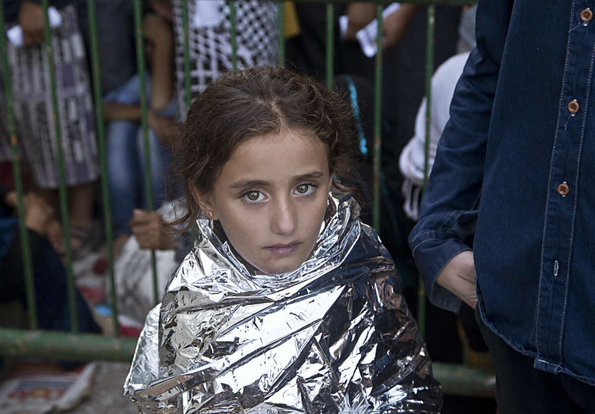 An Afghan migrant girl covered with a Mylar sheet after being rescued waits to be registered at the port office in Mytlilene in Lesbos, Greece, Friday, Aug. 21, 2015. Greece this year has been overwhelmed by record numbers of migrants arriving on its eastern Aegean islands, with more than 160,000 landing so far. (AP Photo/Visar Kryeziu)
