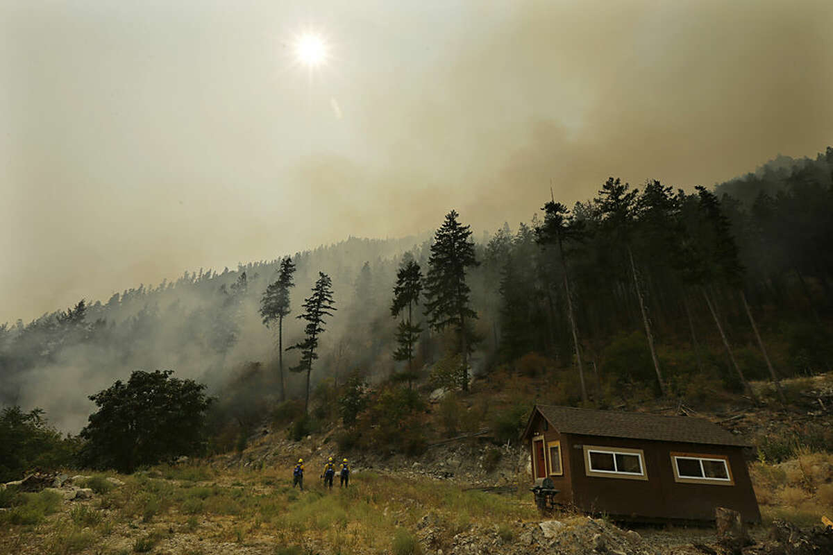 Three Washington National Guard soldiers stand near a structure as they fight the First Creek Fire, Tuesday, Aug. 18, 2015, near Chelan, Wash. The troops in Washington state were part of a massive response to blazes burning throughout the West. (AP Photo/Ted S. Warren)