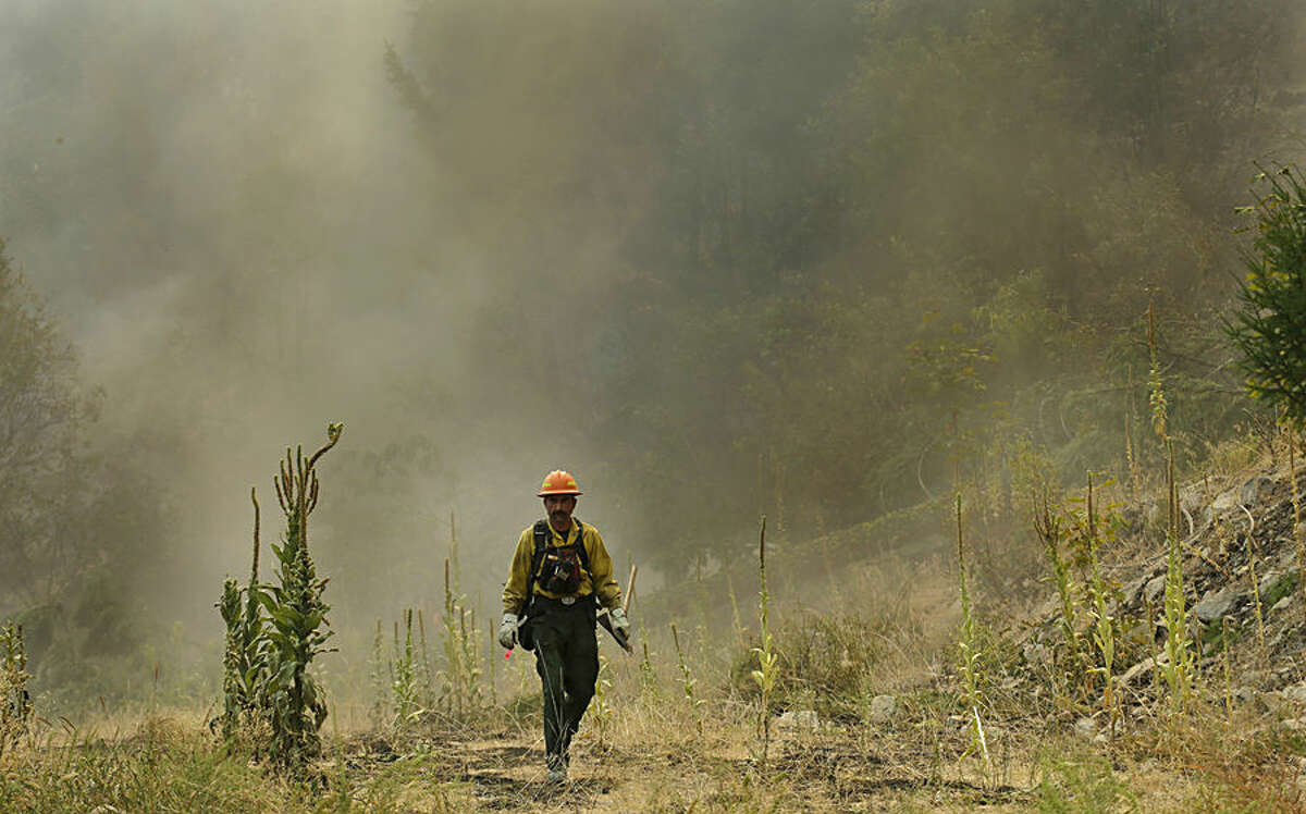 A firefighter walks away from a smoke-filled hillside while fighting the First Creek Fire, Tuesday, Aug. 18, 2015, near Chelan, Wash. Wildfires are putting such a strain on the nation's firefighting resources that authorities have activated the military and sought international help to beat back scores of blazes burning uncontrolled throughout the dry West. (AP Photo/Ted S. Warren)