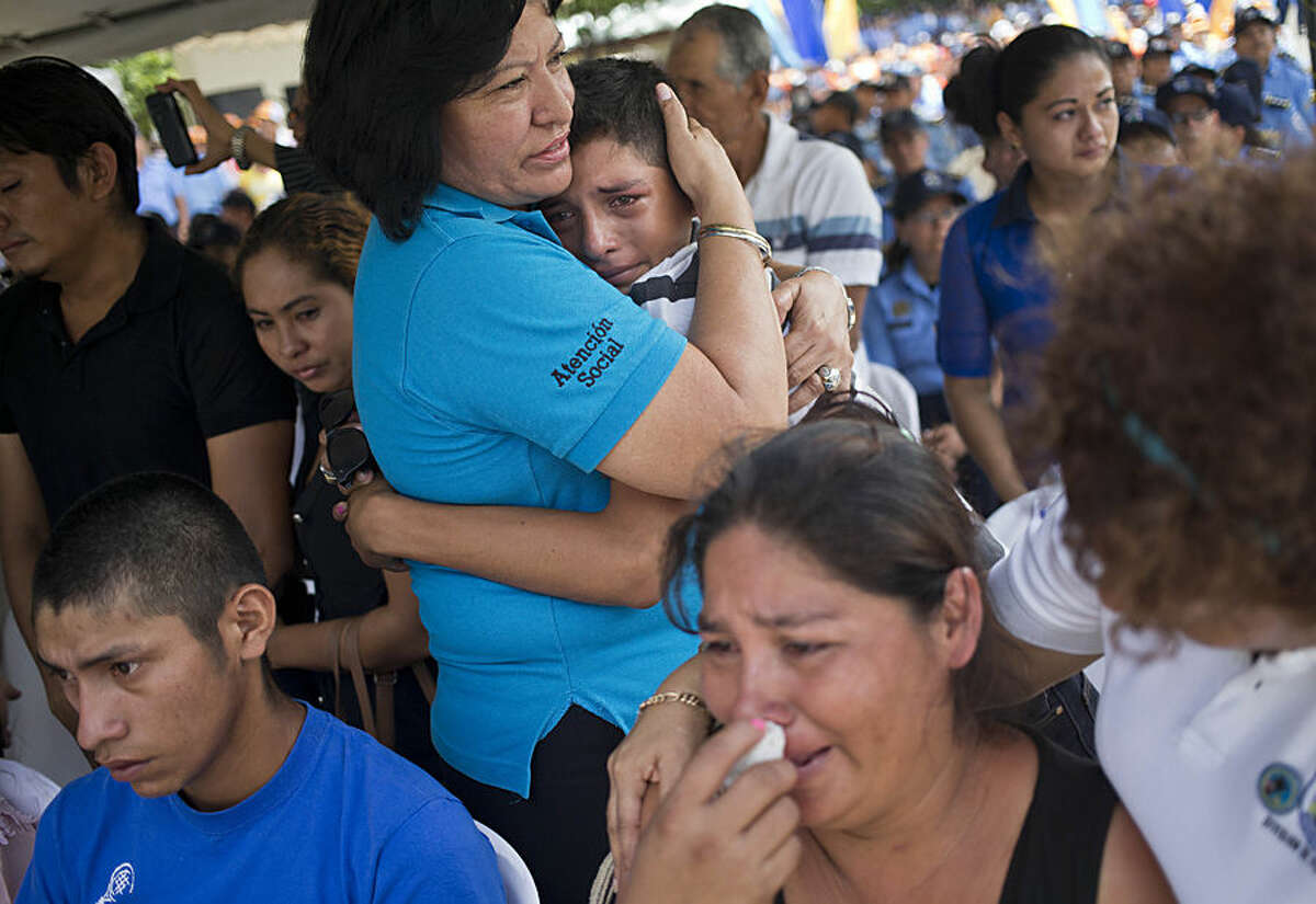 Relatives of the five police officers gunned down in an ambush cry during a ceremony to pay homage to their service, at the Police Headquarters in Managua, Nicaragua, Tuesday, Aug 18, 2015. The five police officers were killed when they where ambushed in the country's southeastern Caribbean jungle by a criminal gang, as they where transporting another member of the gang. (AP Photo/Esteban Felix)