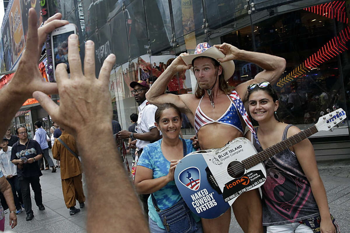 Robert Burck, who performs as the Naked Cowboy, wears a bra as he poses for photos in New York's Times Square, Wednesday, Aug. 19, 2015. New York Gov. Andrew Cuomo says women posing nearly naked for photos in Times Square are breaking the law and undermining efforts to keep the tourist area family friendly. The women pose for photos with tourists in exchange for cash and often wear only body paint and a thong. (AP Photo/Richard Drew)