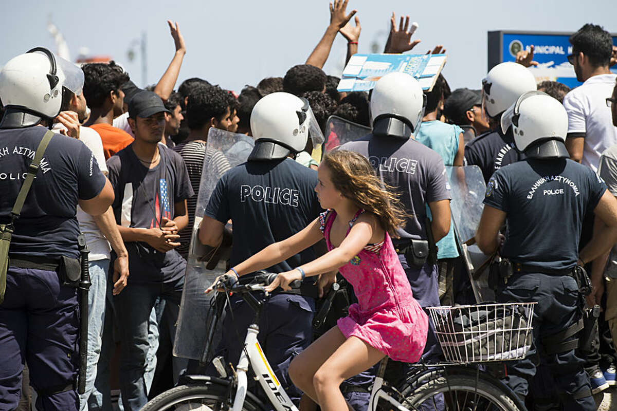 A young tourist rides a bicycle in front of Greek police officers as they block Pakistani migrants waiting to be registered at a polic station on the island of Kos, Greece, Wednesday, Aug. 19, 2015. More than 130,000 migrants have reached Greece so far in 2015, straining the country's resources. (AP Photo/Alexander Zemlianichenko)