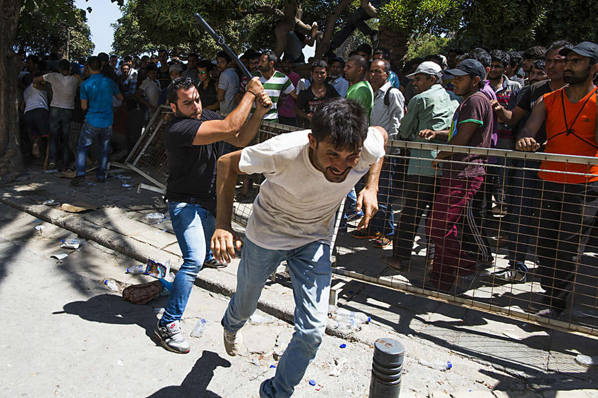 A Greek plain clothed policeman chases away Pakistani migrants as they started shouting while waiting to be registered near a police station at the southeastern island of Kos, Greece, Wednesday, Aug. 19, 2015. More than 130,000 migrants have reached Greece so far in 2015, straining the country's resources. (AP Photo/Alexander Zemlianichenko)