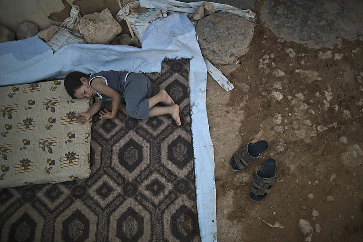 A Syrian refugee child sleeps on the ground outside his family's tent to escape the heat trapped inside, at an informal tented settlement near the Syrian border on the outskirts of Mafraq, Jordan, Wednesday, Aug. 19, 2015. (AP Photo/Muhammed Muheisen)