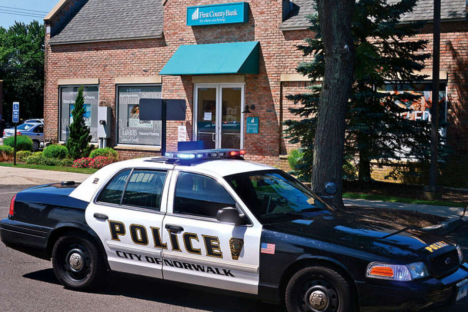 Hour photo / Erik Trautmann Norwalk police investigate a robbery at The First County Bank on Westport Ave Thursday.