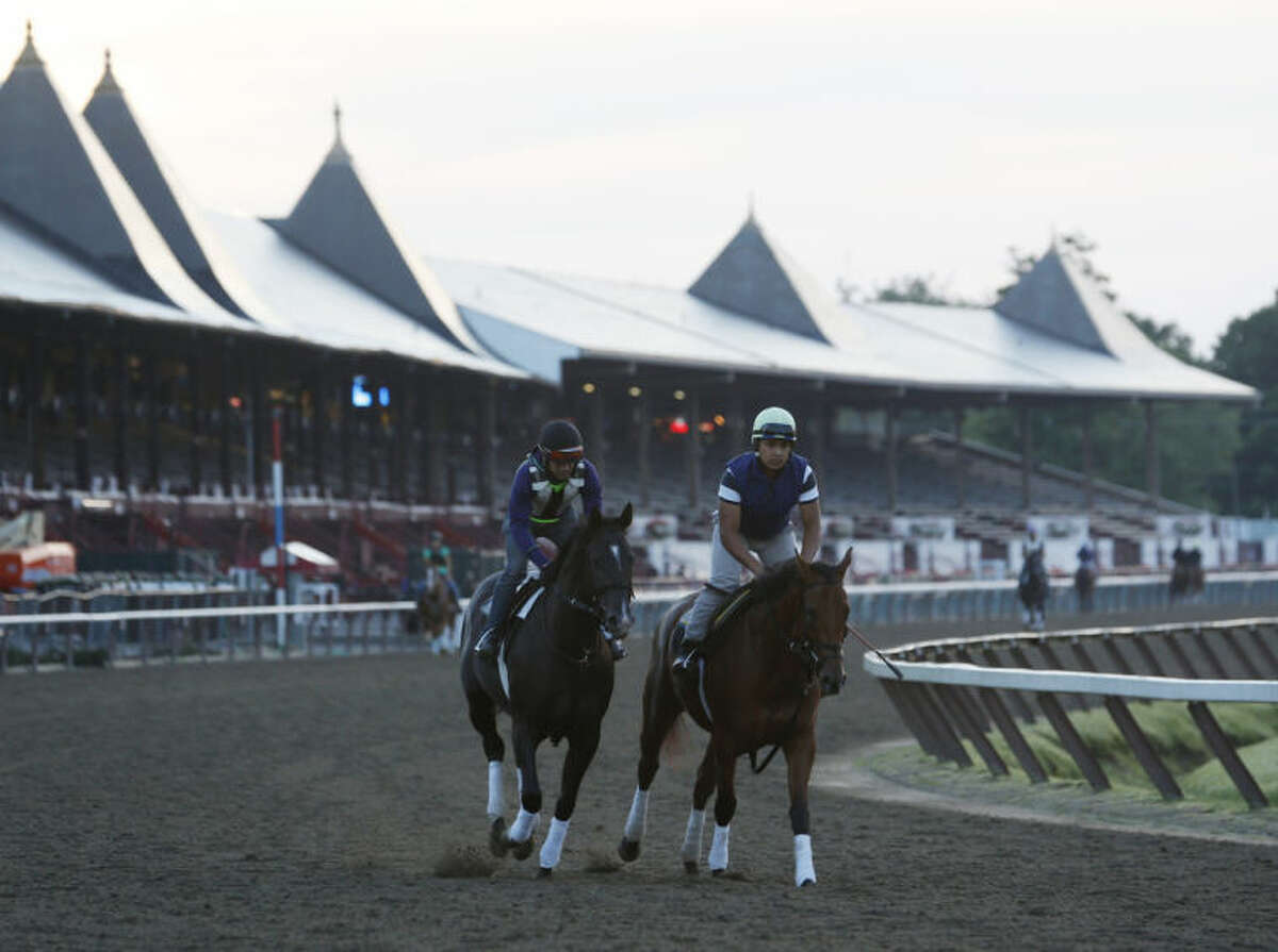 Exercise riders ride horses during morning workouts at Saratoga Race Course on Thursday, July 17, 2014, in Saratoga Springs, N.Y. The Saratoga horse racing meet opens on Friday. (AP Photo/Mike Groll)