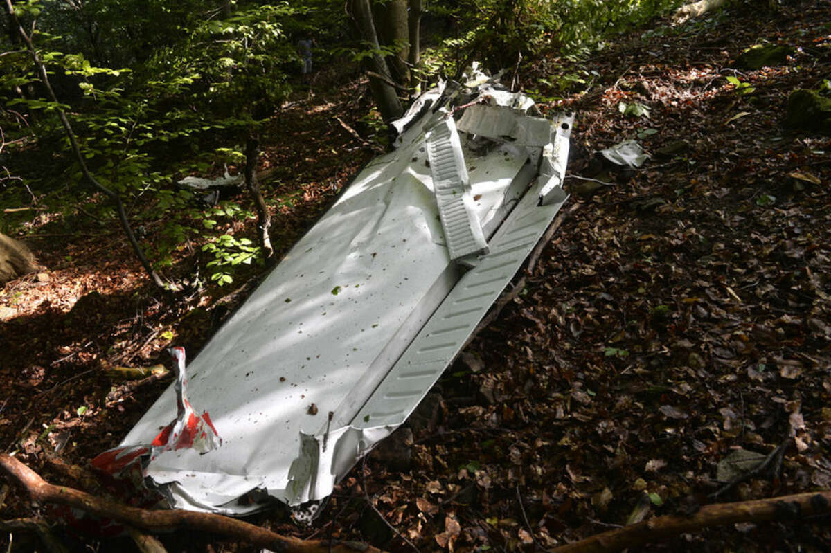A part of the light aircraft that crashed near the village of Cerveny Kamen, Slovakia on Thursday, Aug. 20, 2015. Two planes carrying dozens of parachutists collided in midair over western Slovakia, killing several people, officials said. Slovak media reported more than a dozen other parachutists missing and an aviation official said some reportedly survived by jumping out with their parachutes. ( Radovan Stoklasa /TASR via AP)