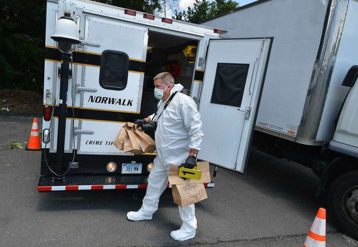 Hour Photo/Alex von Kleydorff After a bank robbery on Westport Ave, Norwalk Police Dept Detective Art Weisberger places bags of collected evidence from the woods off Strawberry Hill Ave into the Evidence Collection Unit.