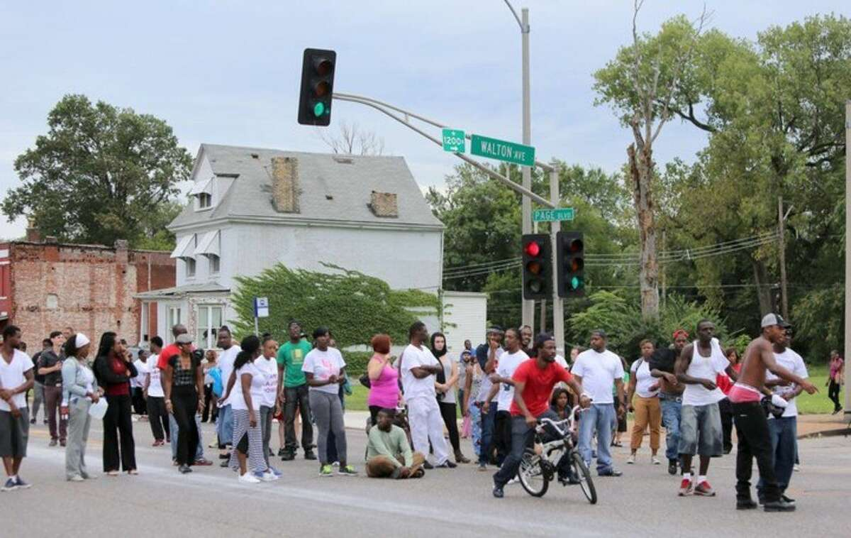 People gather at the scene of a fatal officer-involved shooting at Walton Avenue and Page Boulevard, Wednesday, Aug. 19, 2015 in St. Louis. An armed man fleeing from officers serving a search warrant at a home in a crime-troubled section of north St. Louis was shot and killed Wednesday by police after he pointed a gun at them, the police chief said. (David Carson/St. Louis Post-Dispatch via AP) EDWARDSVILLE INTELLIGENCER OUT; THE ALTON TELEGRAPH OUT; MANDATORY CREDIT