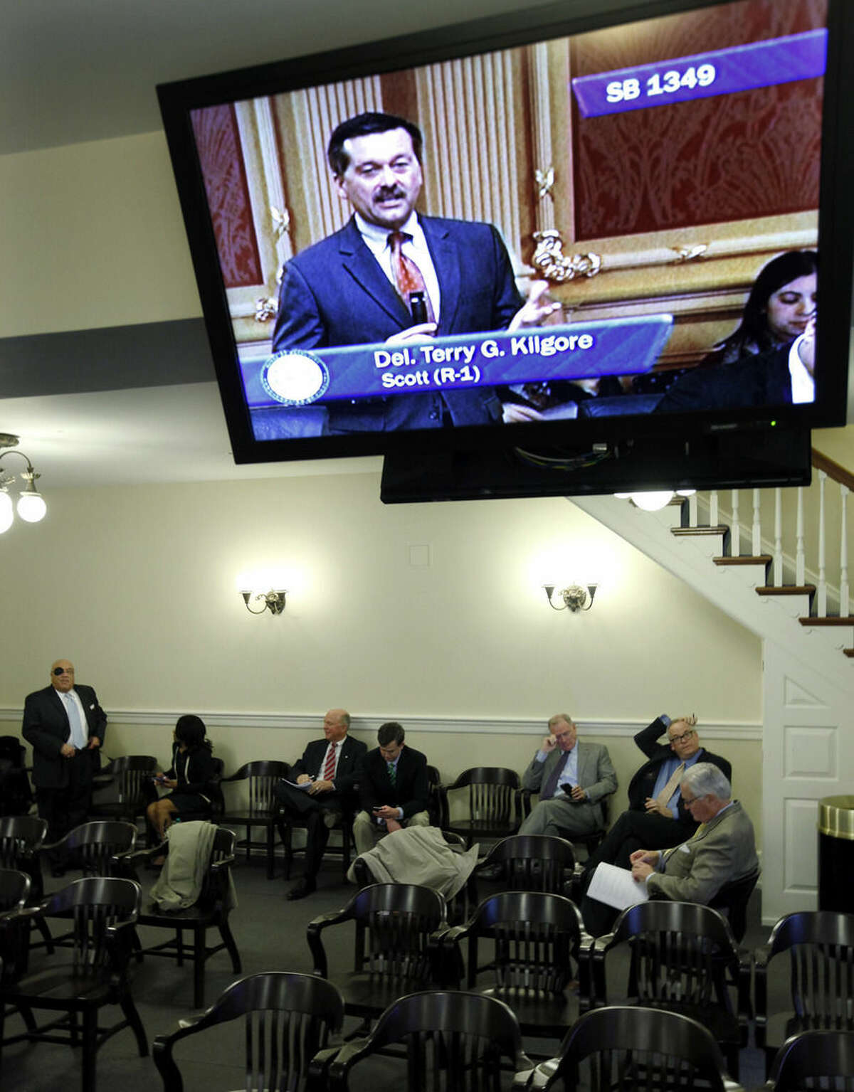 FILE - In this Feb. 12, 2015, file photo, lobbyists for Dominion Resources watch from a committee room as Del. Terry G. Kilgore, R-Scott, (on closed-circuit tv) presents SB1349, a bill from Sen. Frank W. Wagner, R-VA Beach, changing the regulatory structure of electric utility companies, to the members of the Virginia House of Delegates at the State Capitol in Richmond, Va. Company records obtained by the AP show residents were billed tens of thousands to pay for donations Dominion Resources made to politically connected charities. (AP Photo/Richmond Times-Dispatch, Bob Brown, File)
