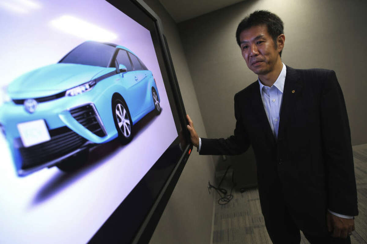 In this July 10, 2014 photo, Toyota Motor Corporation Managing Officer Satoshi Ogiso looks at the image of Toyota FCV fuel cell vehicle during an interview with The Associated Press in Tokyo. Buoyed by its success with electric-gasoline hybrid vehicles, Toyota is betting that drivers will embrace hydrogen fuel cells, an even cleaner technology that runs on the energy created by an electrochemical reaction when oxygen in the air combines with hydrogen stored as fuel. (AP Photo/Eugene Hoshiko)