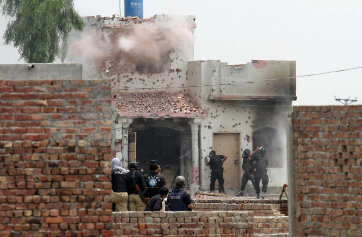 Pakistani police commandos carry out an operation at a militant hideout in Lahore, Pakistan, Thursday, July 17, 2014. Officials said police fought for more than 10 hours with militants planning to attack the prime minister's home in eastern Pakistan. (AP Photo/K.M. Chaudary)