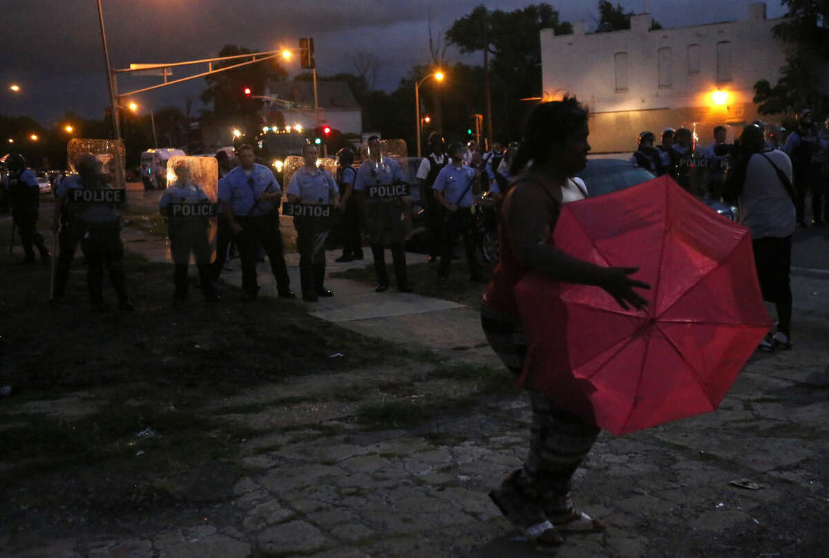 A lady crosses in front of the police line as they stand guard in riot gear where protesters gather on Walton Avenue and Page Boulevard on Wednesday, Aug. 19, 2015, in St. Louis. A black 18-year-old fleeing from officers serving a search warrant at a home in a crime-troubled section of St. Louis was fatally shot Wednesday by police after he pointed a gun at them, the city's police chief said. (Laurie Skrivan/St. Louis Post-Dispatch via AP) EDWARDSVILLE INTELLIGENCER OUT; THE ALTON TELEGRAPH OUT; MANDATORY CREDIT