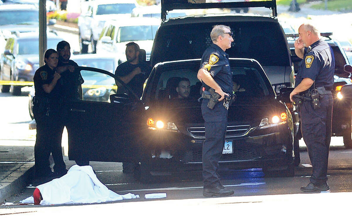 Hour photo/Erik Trautmann Norwalk police investigate the scene after a person fell to their death from the I-95 overpass onto West Avenue in Norwalk Friday afternoon. Police would not confirm or deny whether the incident was a suicide.