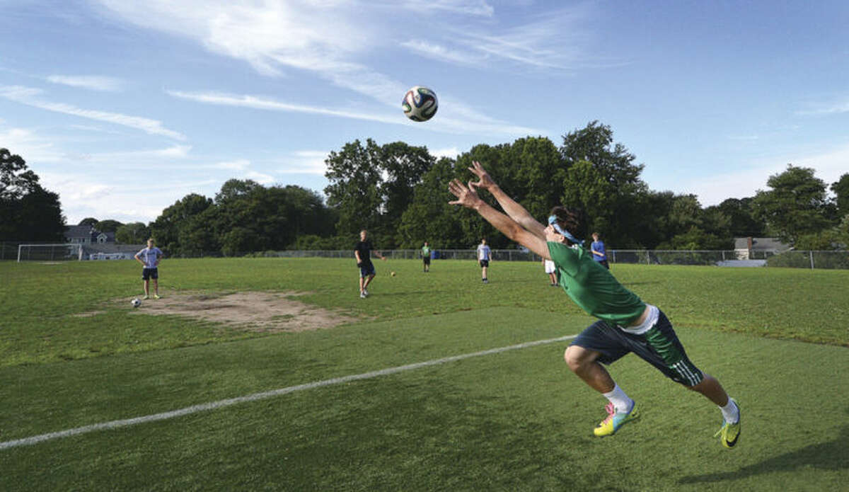 Hour photo/Alex von Kleydorff Michael Waring tries to grab the ball as some of the Norwalk High soccer team play on the field at Nathan Hale Middle School.