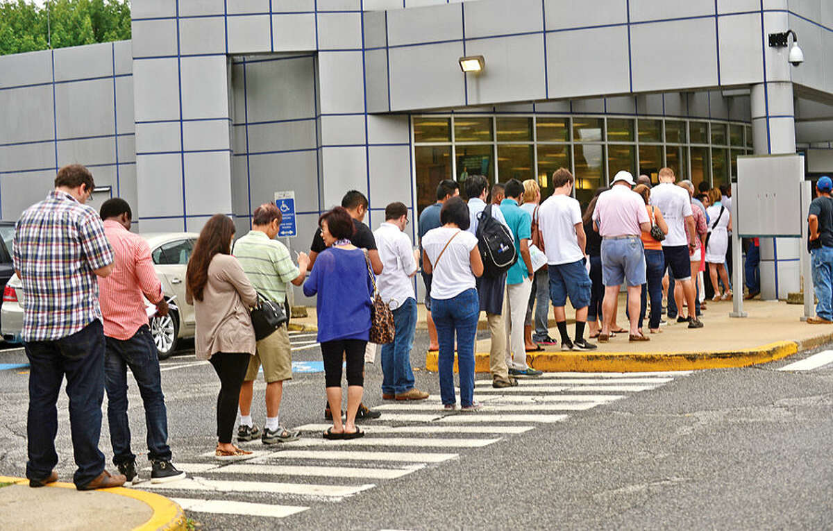 Hour photo / Erik Trautmann Connecticut residents line up at the Norwalk Department of MOtor Vehicles on Main Ave Friday.