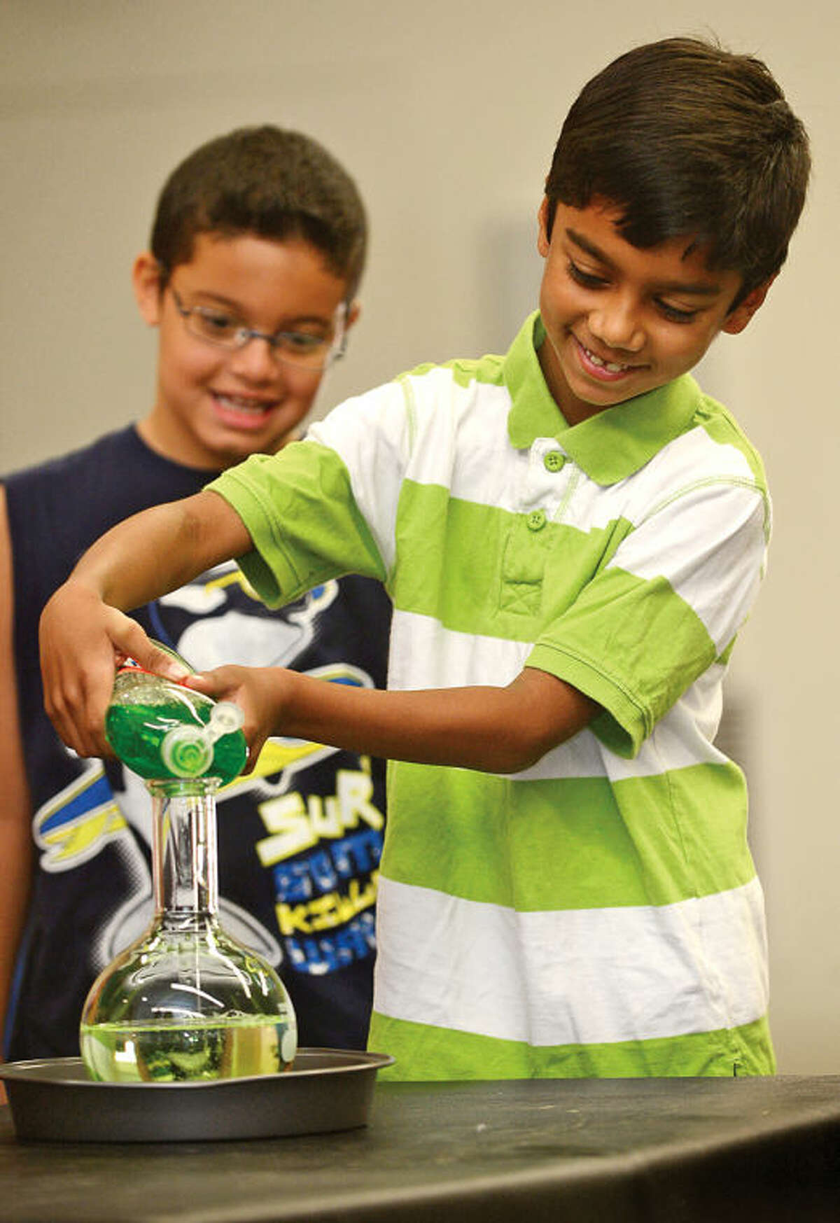 Hour photo / Erik Trautmann Aayush Athavia, 7, conducts an experiment with Interactive science storyteller, Justin Maruri, otherwise known as a Scienceteller, during his presentation